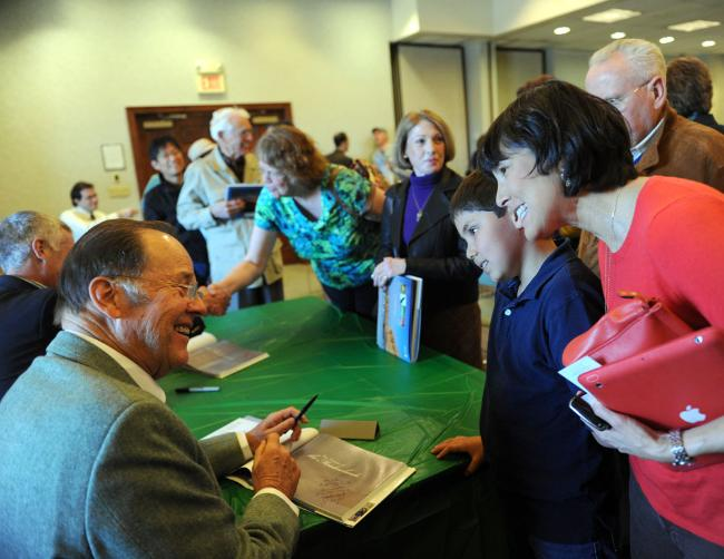 Former Gov. Thomas H. Kean talks with Etan Zeller MacLean, 11, and Susana MacLean of Westfield after signing their copy of 'The Nature of the Meadowlands.'